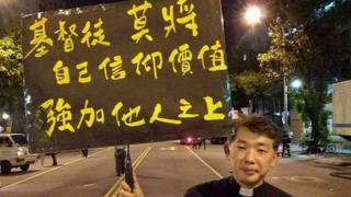 陈思豪牧师举牌,上面写到:基督徒莫将信仰价值强加他人之上