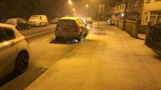 Snow falling in a Belfast street