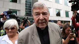 George Pell followed by media as he leaves a Melbourne courtroom on Tuesday after a reporting ban on his conviction was lifted