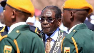 Zimbabwean President Robert Mugabe inspects the guard of honour during a ceremony in Harare, Monday Aug. 10, 2015, honouring thousands of fighters who died in a 1970s Bush war against colonialism.