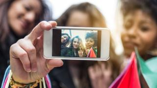 Young people taking a photo with a mobile phone
