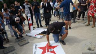 Protesters placing broken star signs outside buildings
