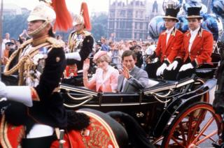 The newly married Prince and Princess of Wale wave to the London crowds from their open-top carriage as they make their way to Waterloo Station to depart for their honeymoon.