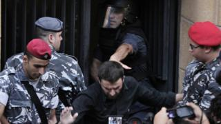 Lebanese riot police eject a protester from the environment ministry