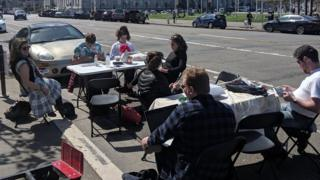 People sit at a desk in a parking space
