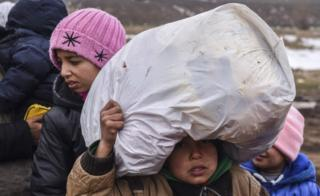 A child migrant holds his belongings as he waits on the Macedonian border into Serbia