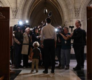 Prime Minister Trudeau gives a statement to the press, flanked by his diminutive offspring, who appears to be distracting some of the reporters.