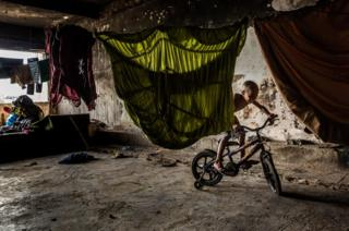 A resident rides his bike in the occupied IBGE building, 'Favela' Mangueira community, Rio de Janeiro, Brazil.