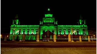 Belfast City Hall lit up with green lights