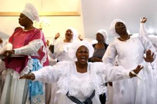 Worshippers sing as they offer thanksgivings during Sunday service