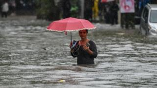 A girl walk along a flooded street after heavy rain showers Gandhi Market, Sion on July 1, 2019 in Mumbai, India. Heavy rains for last four days led to trains disruptions, flooded roads, traffic jams and flight delays.