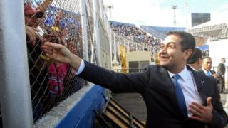 Reelected President Juan Orlando Hernandez waves to the crowd at his arrival to the inauguration ceremony at the Tiburcio Carias Andino national stadium, in Tegucigalpa, on January 27,