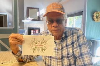 Michael Esmond con una tarjeta navideña enviada por la ciudad