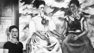 Frida Kahlo frente a uno de sus autorretratos.