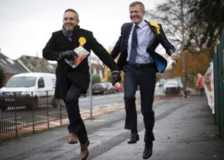 Scottish Liberal Democrat leader Willie Ronnie (right) and party general election campaign chairman Alex Cole-Hamilton skip down a street