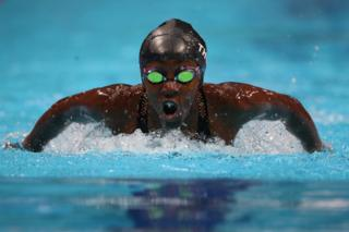 A swimmer takes a deep breath as she surfaces from the water. Her reflective goggles appear green.