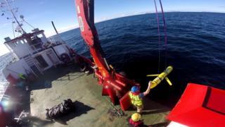 图为美国海军人员在操作无人潜航器。