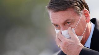 Brazil's President Jair Bolsonaro adjusts his mask as he arrives to a national flag hoisting ceremony