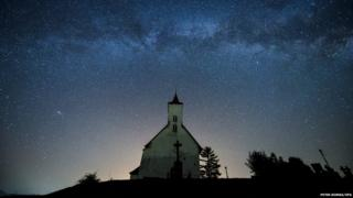 A church is silhouetted below the Milky Way