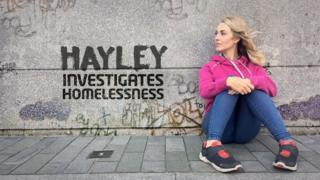 Reporter Hayley looks to her right, sitting on the ground next to a wall covered in graffiti. Next to her are the words 'Hayley investigates homelessness'