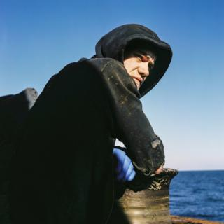 A man in a worn hoodie looks out to sea