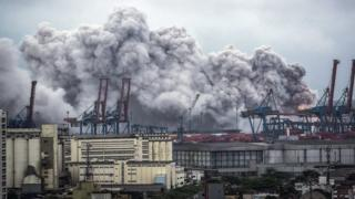A general view over the port on a giant cloud of smoke billowing in Guaruja, near Santos, Sao Paulo, Brazil, 14 January 2016. According to reports, the smoke was caused by a chemical reaction of Dichloroisocyanuric acid in contact with water that entered a cargo container. EPA