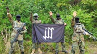 Men in army fatigues and masks holding neo-Nazi flags in the countryside