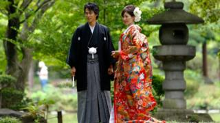 In this Aug. 12, 2015 file photo, a couple dressed in Japanese traditional wedding Kimonos pose for a wedding photograph at Hibiya park in Tokyo.