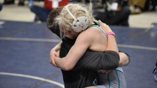 A teenage girl dressed in amateur wrestling gear hugging an older man