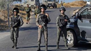 חיילים ישראלים עומדים על המשמר ליד האתר בו נמצאה גופתו של חייל ישראלי