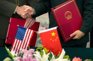 Close up of US and Chinese official shaking hands, holding documents. Flags of both countries in the foreground
