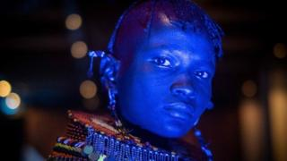 A dancer of Turkana tribe performs in blue light during the launching ceremony of the 11th Marsabit-Lake Turkana Cultural Festival in Nairobi, Kenya, on June 20, 2018.