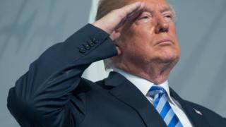 US President Donald Trump salutes during a US Coast Guard ceremony