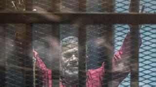 Mohammed Morsi gestures from behind bars during a trial in Cairo on 23 April 2016