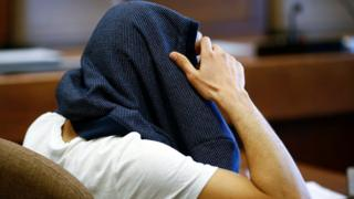 A 26-year-old Algerian who faces charges of assaults on woman during New Year's Eve celebrations in Cologne, covers his head at a regional court in Cologne, western Germany, May 6, 2016