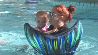 Alannah being held by lady in a pool with mermaid tail