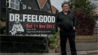 Chris Fenwick beside a Dr Feelgood poster