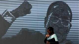 A young boy walks past a digital image of late former Zimbabwean president Robert Mugabe as his body lies in state at Murombedzi Growth Point, about 107 km northwest of Harare, Zimbabwe, on September 16, 2019