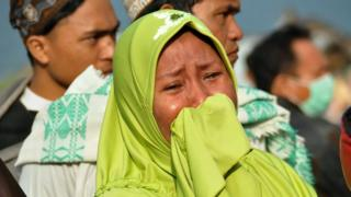 A woman cries as people look at the damages after an earthquake and a tsunami hit Palu