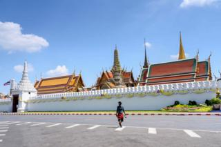 A man wearing a mask crosses a deserted street in front of the Grand Palace in Bangkok