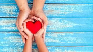 Dos manos entregan un corazón.