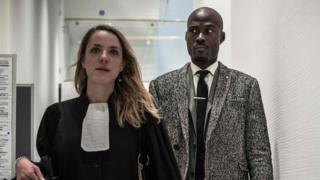 "French rapper Nick Conrad and his lawyer arrive at court for his trial over a video entitled ""Hang the Whites"""
