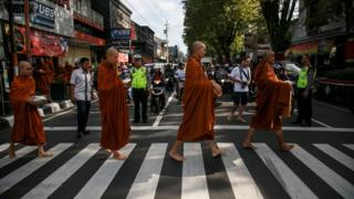 Buddhist monks walk across a street while collecting alms ahead of Vesak day in Magelang, Central Java, Indonesia May 28, 2018