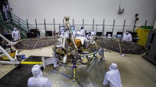 Foto mostra dezenas de funcionários com máscaras e jalecos brancos trabalhando com grandes equipamentos que compõem a missão InSight
