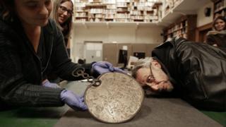 Michael Rosen inspects the Desborough Mirror - similar to the Portesham Mirror