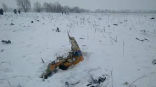 На фотографиях с места катастрофы видны обломки самолета на заснеженном поле