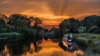 Sun sets behind a lake. Two people are on a canal boat