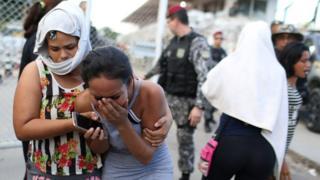 Mulheres choram e se consolam do lado de fora de presídio em Manaus, com agentes de segurança e cerca aparecendo ao fundo
