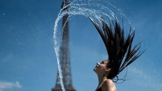 A woman plays the water as she cool herself down in the fountain of the Trocadero esplanade in Paris on June 25, 2019