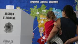 Eleitora com a filha no colo, ao lado de uma sessão de votação, e em frente a um mapa do Brasil com o nome das 5 regiões
